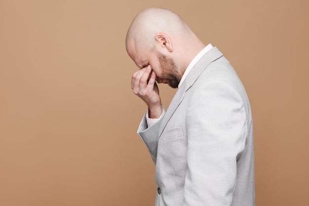 明るい灰色のスーツに立って、手を閉じて目を閉じて悲しい泣いている中年の禿げたひげを生やしたビジネスマンの縦断的な側面図の肖像画。薄茶色の背景に分離された屋内スタジオショット。