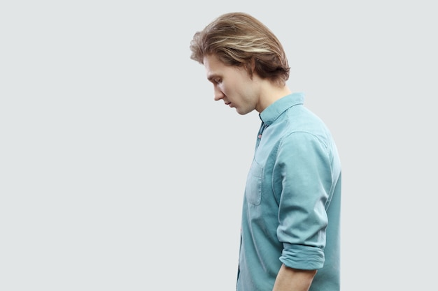 頭を下げて立って気分が悪い青いカジュアルなシャツを着た悲しいハンサムな長い髪の金髪の若い男の縦顔の側面図の肖像画。明るい灰色の背景に分離された屋内スタジオショット。