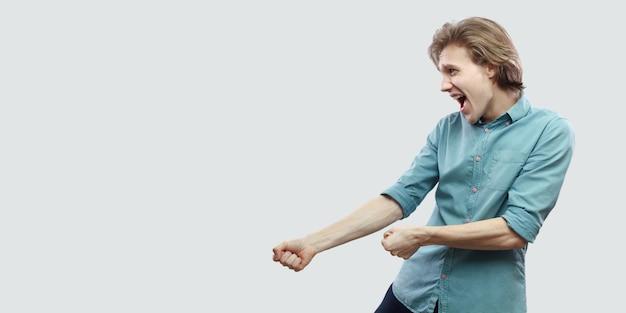 권투 제스처 또는 당기는 시각화와 함께 서 있는 파란색 셔츠에 잘생긴 장 발 금발의 젊은 남자의 프로필 측면 보기 초상화. 밝은 회색 배경에 고립 된 실내 스튜디오 촬영