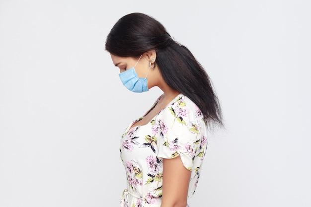 頭を下げて立っている白いドレスを着た医療マスクを持った若い悲しい一人のブルネットの女性の横顔の側面図の肖像画。問題、気分の悪さ、うつ病の概念。灰色の背景で隔離された屋内。