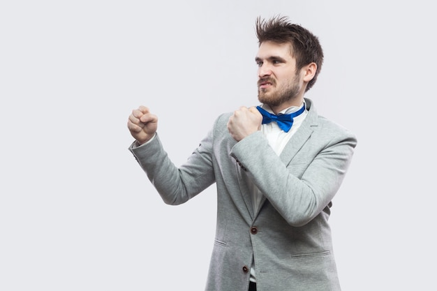 Profile side view portrait of serious handsome bearded man in casual grey suit and blue bow tie standing with boxing fists and looking straight. indoor studio shot, isolated on light grey background.