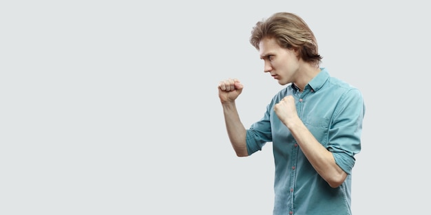 Profile side view portrait of serious handsome long haired blonde young man in blue casual shirt standing with boxing gesture and ready to attack. indoor studio shot, isolated on light grey background