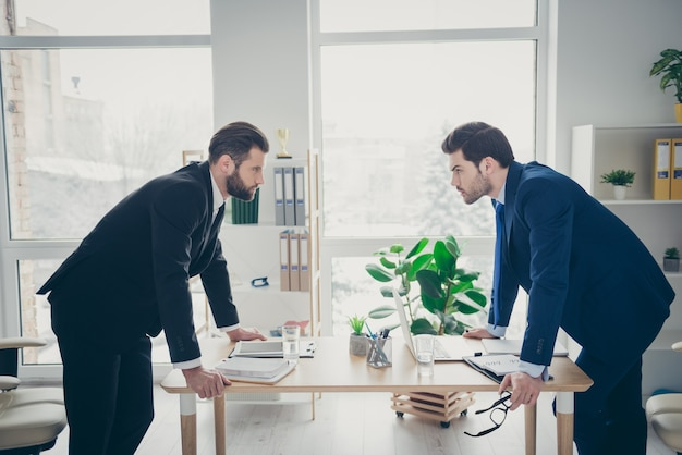 Profile side view portrait of two nice attractive handsome confident serious focused men lawyer attorney competition contest motivation in light white interior workplace workstation