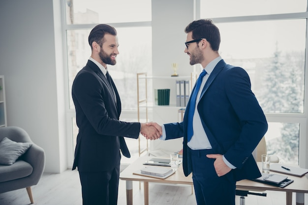 Profile side view of two nice attractive ambitious trendy imposing cheerful cheery men expert employer hr ceo boss chief shaking hands hiring talent at light white interior workplace workstation