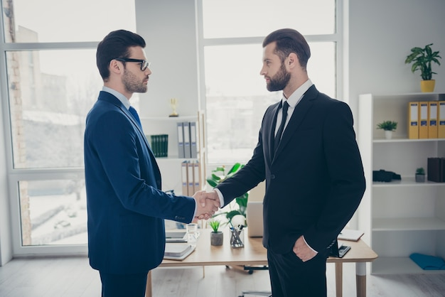 Profile side view of two nice attractive content trendy imposing men qualified finance expert employer hr shaking hands hiring talent human resources at light white interior workplace workstation