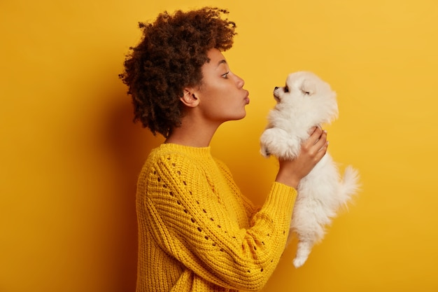 Profile sideways shot of lovely dark skinned woman holds white fluffy spitz cub over face, wants to kiss lovely pet, blows mwah, wears knitted sweater pose against yellow background.