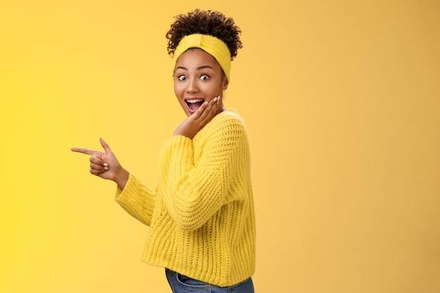 Profile studio shot amused impressed speechless cute stylish shopping girl drop jaw amazed widen eyes turning camera surprised cover open mouth palm pointing left index finger show cool promo.