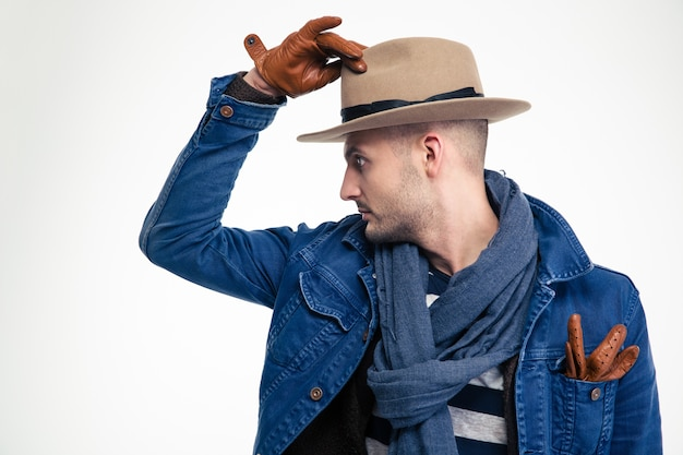 Profile of stylish attracive young man in hat and gloves isolated over white wall
