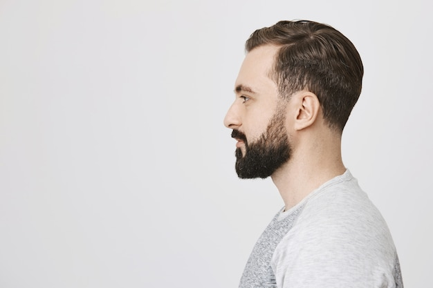 Profile of stylish bearded man made new hairstyle at barber shop