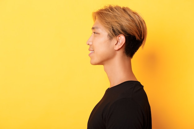 Profile of stylish handsome asian guy with fair hair looking left and smiling, standing over yellow wall