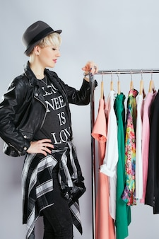 Profile of stylist in fashionable outfit standing near dresses on rack, full body. person in sphere of fashion choosing clothes. shopping, indoors, buying of clothes