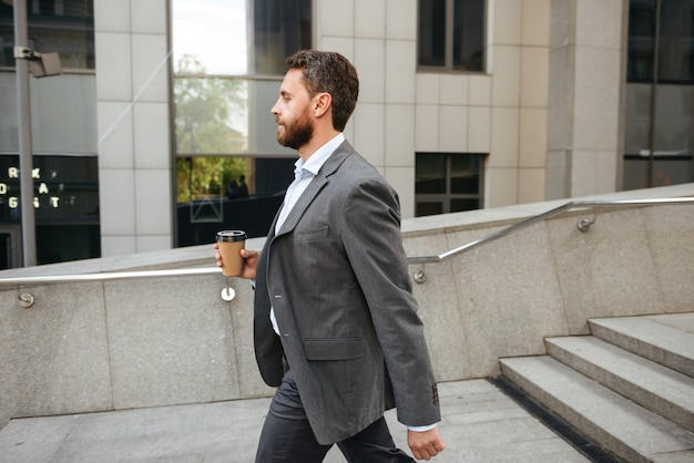 Profile successful entrepreneur or director man in gray suit holding takeaway coffee, and walking along street with modern business center