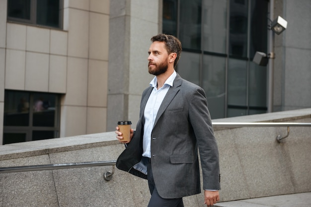 Profile successful executive director or businessman in gray suit holding takeaway coffee, and walking along street with modern business center