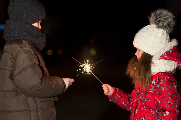 Profile of two cute young children, boy and girl in warm winter clothing holding burning sparkler fireworks on dark night outdoors copy space background. new year and christmas celebration concept.