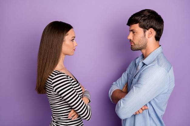 Profile two people couple guy lady standing opposite angry looking eyes arms crossed had fight wear stylish casual outfit isolated pastel purple color wall