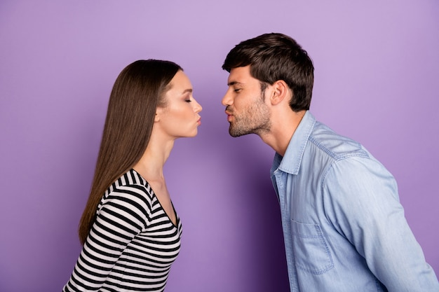 Profile two people couple guy lady standing opposite eyes closed romance moment kissing affectionate wear stylish casual outfit isolated pastel purple color wall