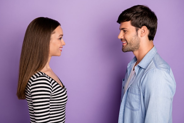 Profile two people couple guy lady standing opposite looking eyes friendly smiling finally meet wear stylish casual outfit isolated pastel purple color wall