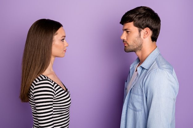 Profile two people couple guy lady standing opposite looking eyes have conflict situation wear stylish casual outfit isolated pastel purple color wall