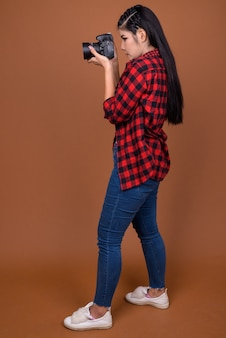 Profile view of asian woman photographer taking picture