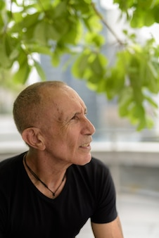 Profile view of bald senior tourist man thinking and relaxing