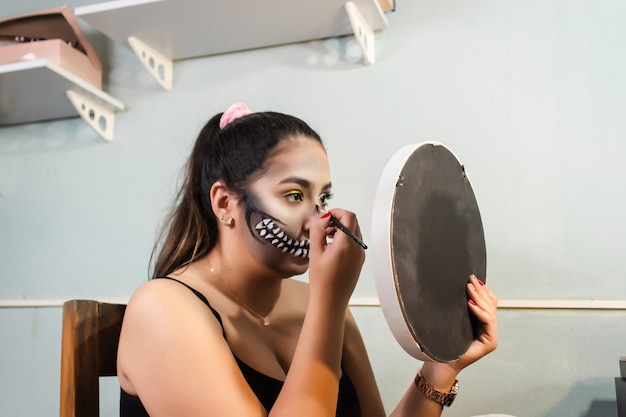 Profile view of a beautiful girl doing her skull teeth makeup for halloween with her little mirror in her room.