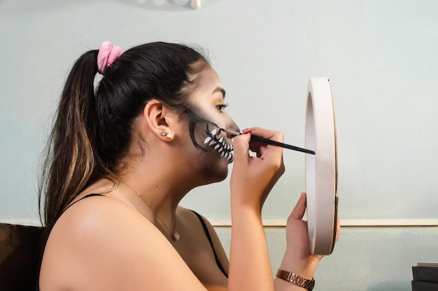 Profile view of a beautiful girl putting skull teeth makeup on her lips for halloween in her bedroom.
