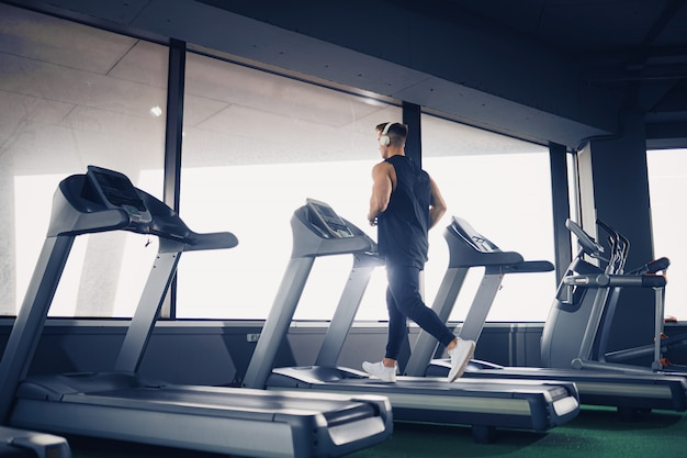 Profile view of concentrated fit man listening to music in headphones while running on treadmill in modern gym with panoramic windows, portrait shot.