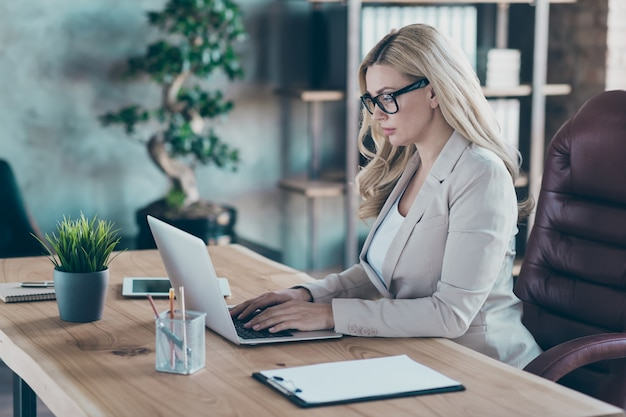 Profile view of confident business lady typing pc