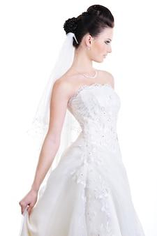 Vista di profilo di elegante bella sposa in abito bianco di bellezza