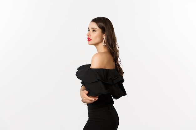 Profile view of elegant young woman with red lips, makeup and black dress, looking dreamy in distance, standing over white background.