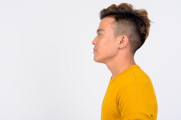 Profile view of face of young asian man against white wall