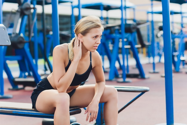 Profile view of female athlete doing some tricep dips on park bench.