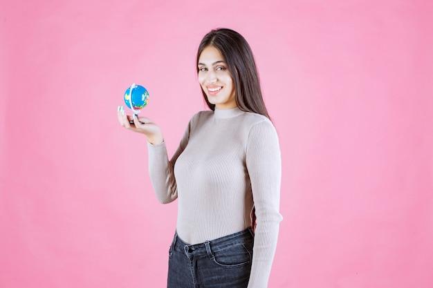 Vista di profilo di una ragazza che tiene un mini globo con fiducia