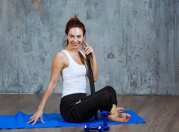 Vista di profilo di una ragazza seduta su un tappetino da yoga blu con strumenti di pilates intorno.