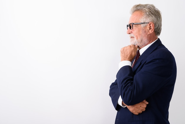 Profile view of handsome senior bearded businessman thinking while wearing eyeglasses on white