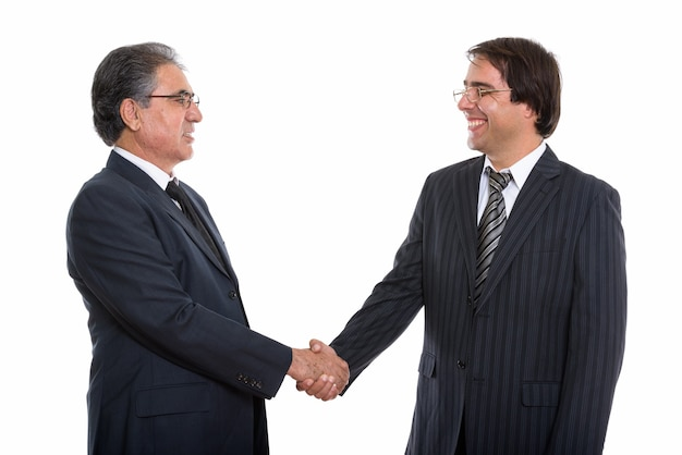 Profile view of happy young and senior persian businessman smiling and handshaking