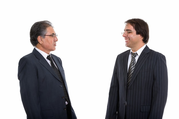 Profile view of happy young and senior persian businessman smiling and looking each one