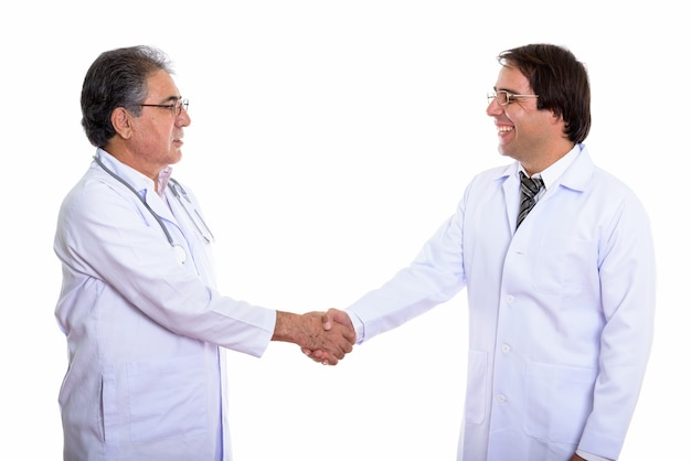 Profile view of happy young and senior persian man doctor smiling and handshaking