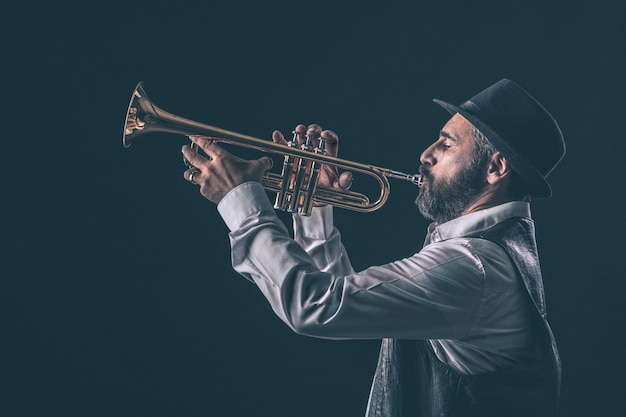 Profile view of a jazz trumpet player with beard and hat.