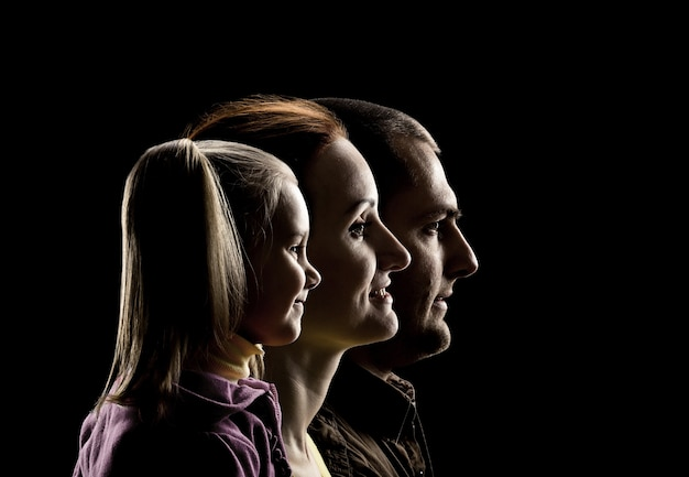 Profile view of little daughter, mother and father over black background