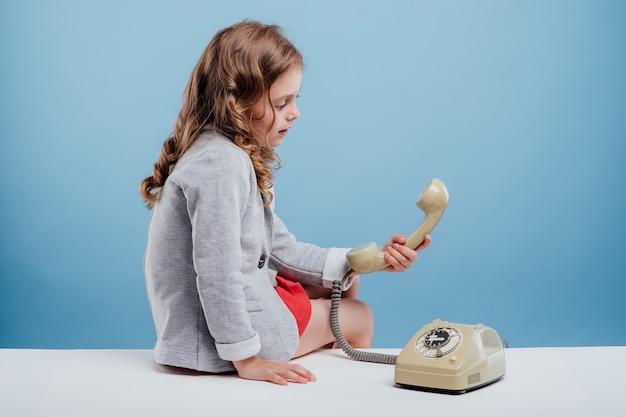 프로필 보기 어린 소녀와 테이블 파란색 배경에 앉아 오래 된 전화