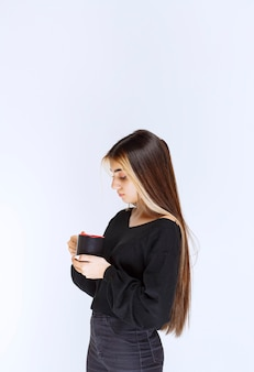 Вид профиля девушки, держащей кружку кофе. фото высокого качества