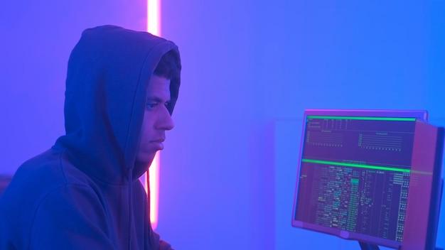 Профиль африканского хакера в толстовке с капюшоном, работающего в комнате с дисплеями и теплой цветовой гаммой ...