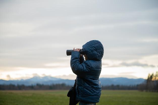 쌍안경을 통해 찾고 아름다운 자연에 밖에 서 흥분된 유아 소년의 프로필보기.