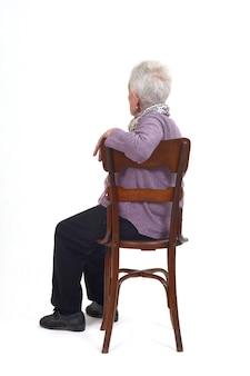 Вид профиля пожилой женщины, сидящей и оглядывающейся на белый фон