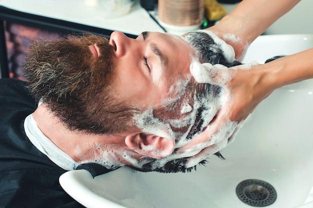 머리를 씻고 머리를 미용실에서 마사지하는 수염 난 남자의 프로필 보기. 미용실에서 머리를 씻는 잔인한 백인 남자의 클로즈업. 이발사 세척 헤드 클라이언트.