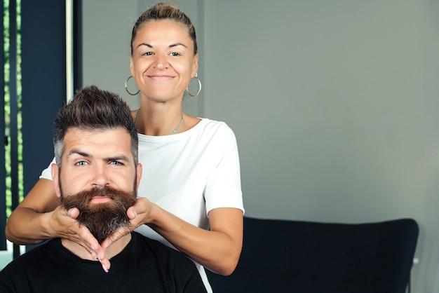 수염을 기른 남자가 수염을 씻고 미용실에서 마사지를 받는 모습. 미용실에서 수염을 씻는 남성 고객의 초상화.