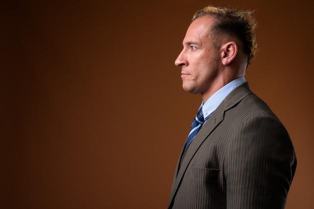 Вид профиля бизнесмена на коричневом