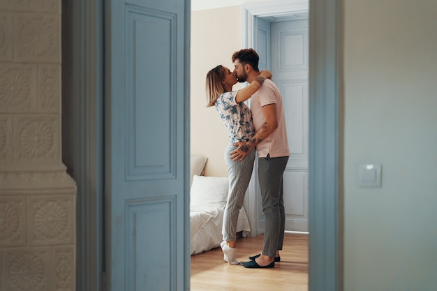 彼らの寝室に立っている間抱いて愛する若いカップルのプロフィール