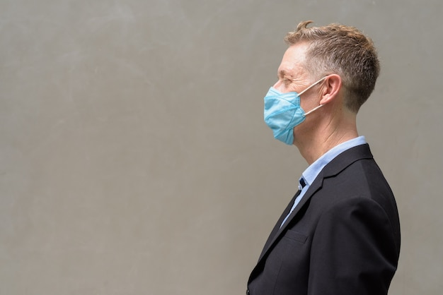 屋外コロナウイルスの発生からの保護のためのマスクを持つ成熟した実業家のプロフィール